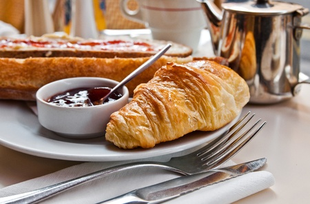 Breakfast with coffee and croissants in a basket on table Stock Photo - 10724164