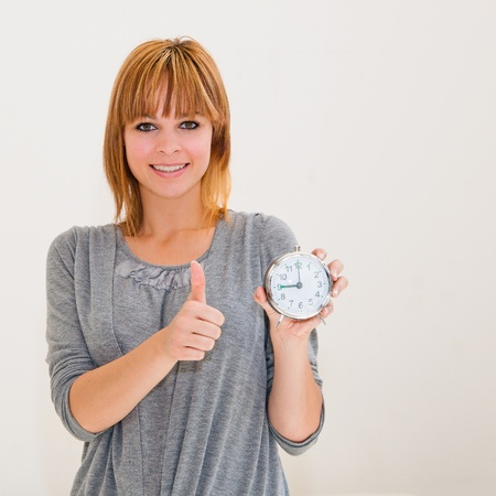 beautiful young woman holding alarm clock with thumbs up photo