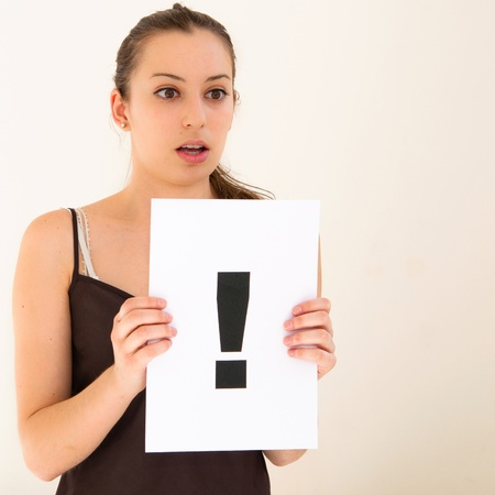 raised eyebrow: portrait young woman with board exclamation point Stock Photo