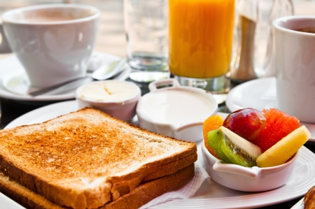 pan frances: Desayuno con zumo de naranja y frutas frescas en la mesa