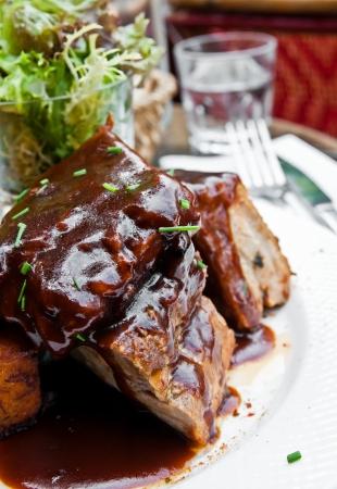 rib: Bistecca alla griglia - le costole a base di carne alla griglia sulla piastra con salsa piccante Archivio Fotografico