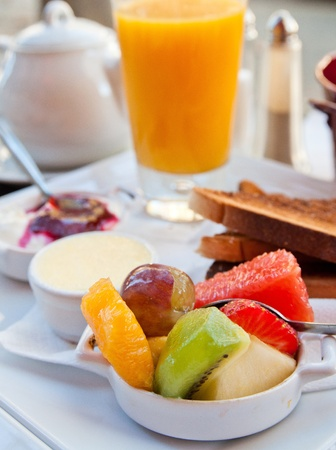 french roll: Breakfast with orange juice and fresh fruits on table