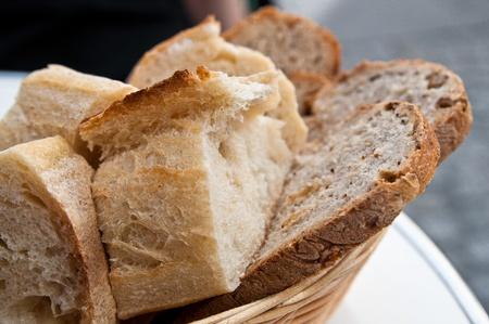 canasta de panes: pan en la canasta - pequeños panes rollo en la cesta sobre la mesa Foto de archivo