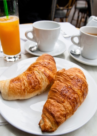 Breakfast with coffee and croissants in a basket on table Stock Photo - 11131704