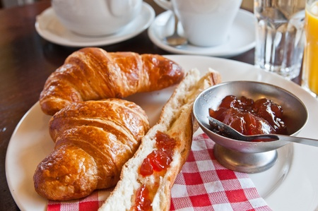traditionally french: Breakfast with coffee and croissants in a basket on table Stock Photo