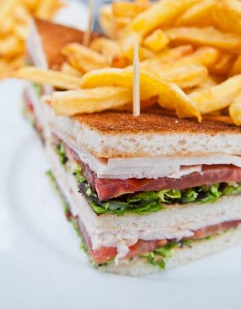 lunchen: Sandwich met kip, kaas en gouden friet aardappelen Stockfoto