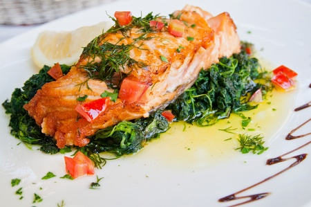 cooked fish: grilled salmon and lemon - french cuisine dish with tomato and salmon