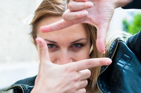Jonge vrouw is gericht zicht in de zoeker gebaren Stockfoto