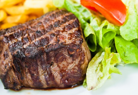 grilled steak: juicy steak beef meat with tomato and french fries