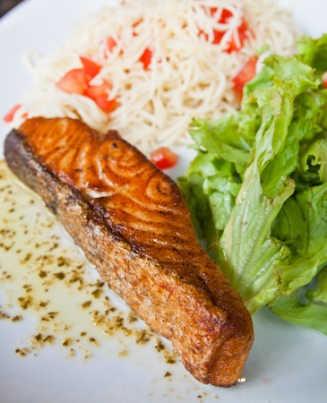 grilled salmon - french cuisine dish with tomato and salmon photo