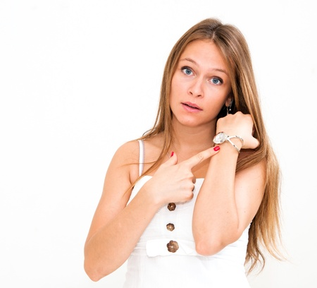 beautiful young woman checking the time on her wrist watch photo