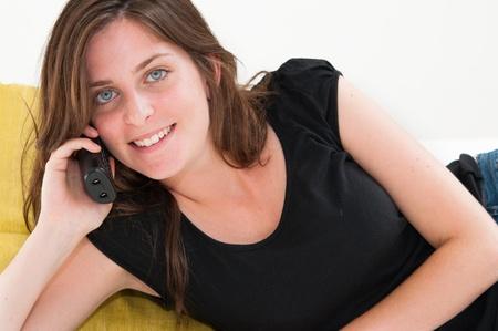 Beautiful happy woman on a white sofa making a phone call photo