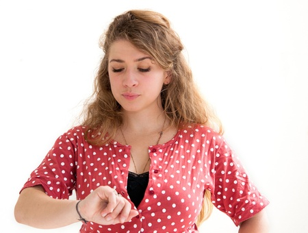 beautiful young woman checking the time on her wrist watch Stock Photo - 12626257