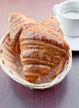 Breakfast with coffee and croissants in a basket on table Stock Photo - 12847184