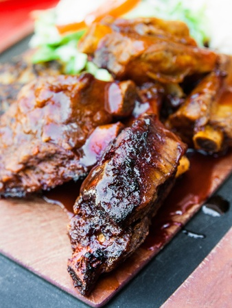 Grilled steak - Grilled meat ribs on the plate with hot sauce photo