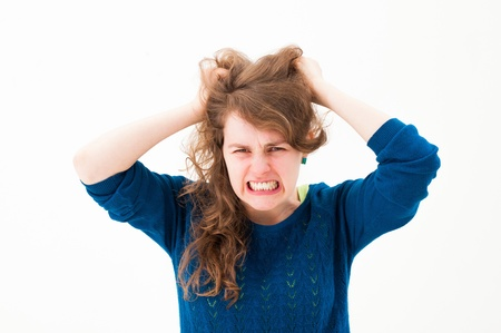 pulling hair: crazy woman making a face and pulling hair on white background