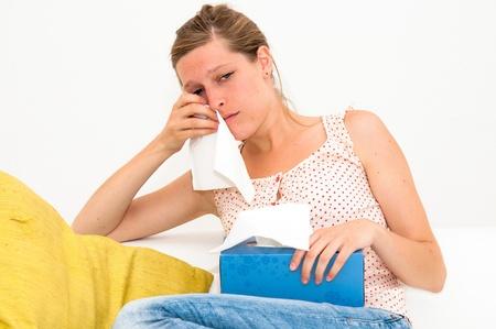Sad woman with tissues on white background photo