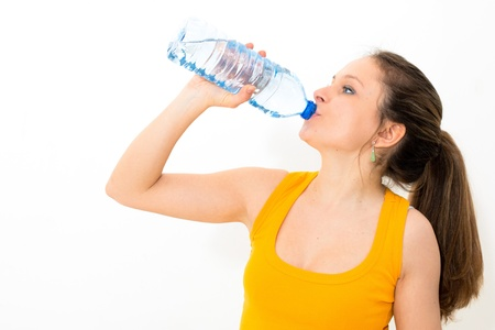Young woman drinking water against white background Stock Photo - 13428387