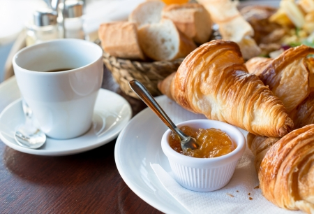 caffeine: Breakfast with coffee and croissants in a basket on table Stock Photo