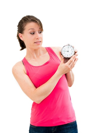 shocked,young beautiful woman holding a clock on a white background photo