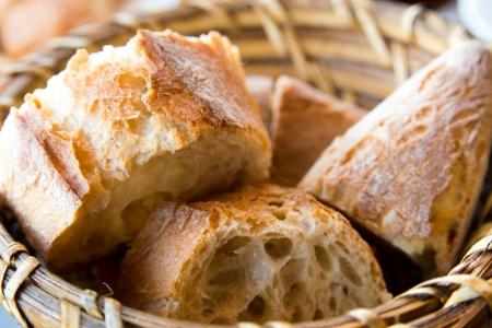 canasta de panes: pan en la cesta - panes pequeños rollos en la cesta sobre la mesa Foto de archivo