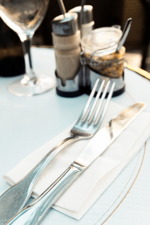 place setting - plate, knife and fork on table photo
