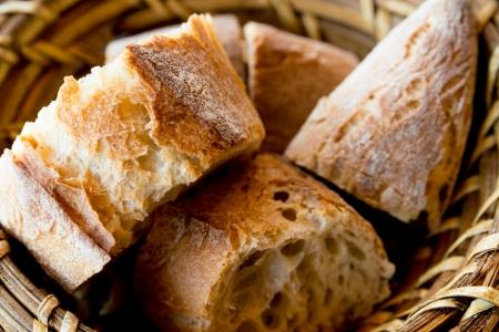 canasta de pan: pan en la cesta - panes pequeños rollos en la cesta sobre la mesa Foto de archivo