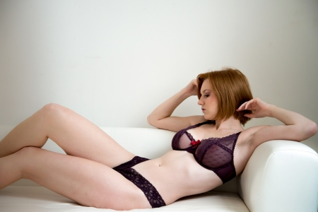 beautiful woman in lingerie relaxing on a sofa photo