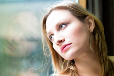 Beautiful woman standing by a window looking outside photo