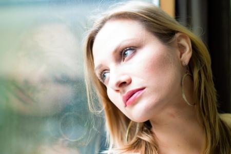 Schöne Frau, die durch ein Fenster nach draußen