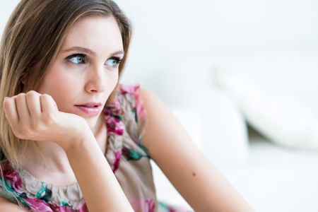 portrait of young woman holding her face on the couch in the living room Stock Photo - 15803856