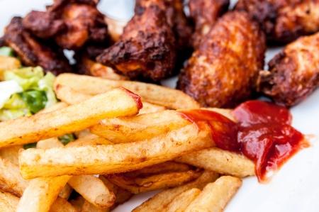 Chicken Wings mit Sauce und goldenen Französisch frites Kartoffeln