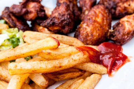 fries: Chicken wings with sauce and golden French fries potatoes
