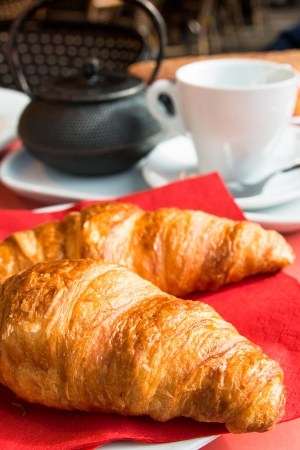 Breakfast with coffee and croissants in a basket on table Stock Photo - 16083663