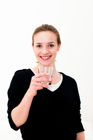 Young woman drinking water against white background photo