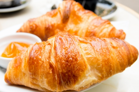 pastry: Breakfast with coffee and croissants in a basket on table Stock Photo