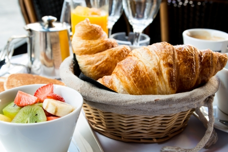 Breakfast with coffee and croissants in a basket on table photo