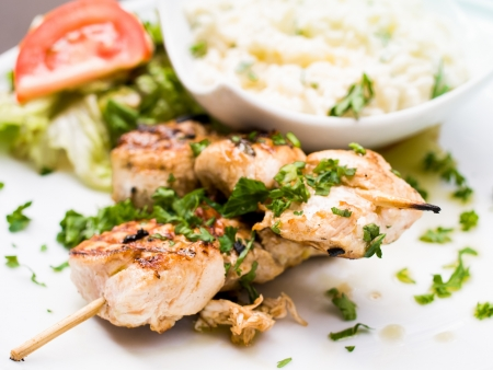 Chicken skewers with sauce and golden French fries potatoes photo