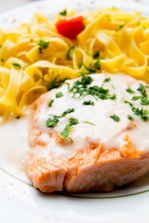 tasty pasta with salmon on a the table photo