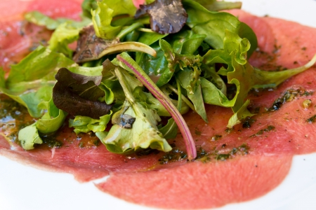 Fresh Sliced raw beef meat with leaf lettuce on table photo