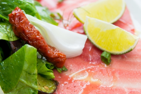 laureate: Fresh Sliced raw beef meat with leaf lettuce on table Stock Photo