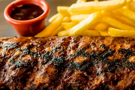 Grilled steak - costillas a la parrilla de carne en el plato con salsa picante photo