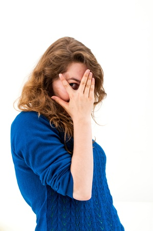 woman shuts face with hands on white background photo