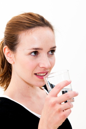 Young woman drinking water against white background Stock Photo - 18098671