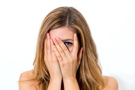 woman hiding face laughing timid on white background photo