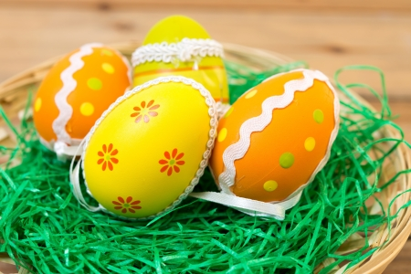 Colorful easter eggs in basket on spring green grass photo