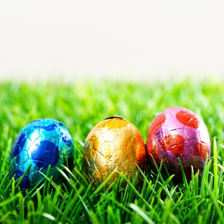 Colorful chocolate easter eggs on green grass photo