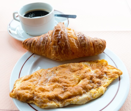 buttery: Breakfast with coffee and croissants in a basket on table Stock Photo