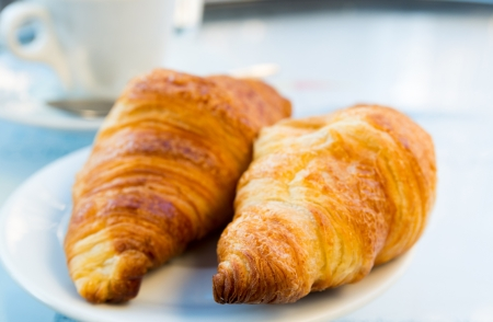 Breakfast with coffee and croissants in a basket on table Stock Photo - 18689458