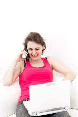 woman on the couch, using her laptop and talking on the telephone photo